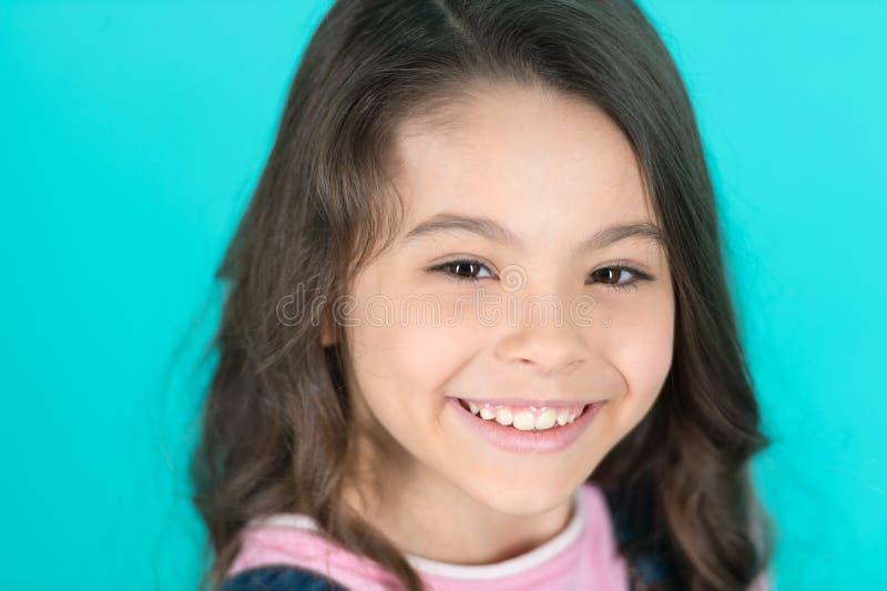 精采微笑 孩子愉快无忧无虑享受童年 儿童迷人的精采微笑绿松石背景 长孩子的女孩 免版税库存照片