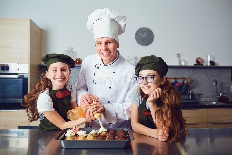 糕点工与女孩孩子准备曲奇饼在厨房里 免版税库存照片
