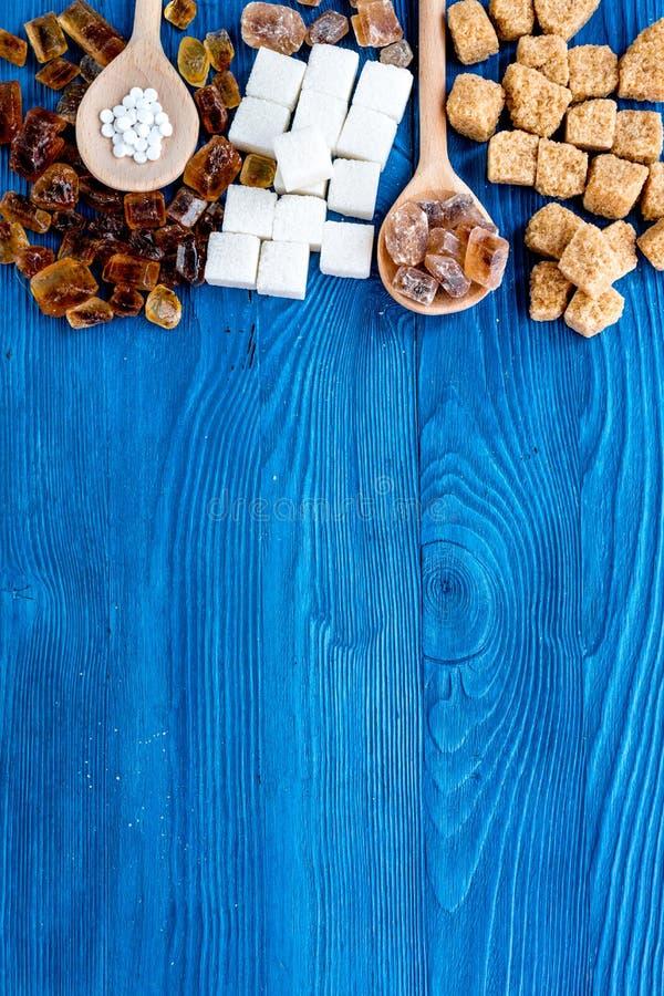 糖与匙子甜点的在蓝色桌背景顶视图大模型设置了 免版税库存照片