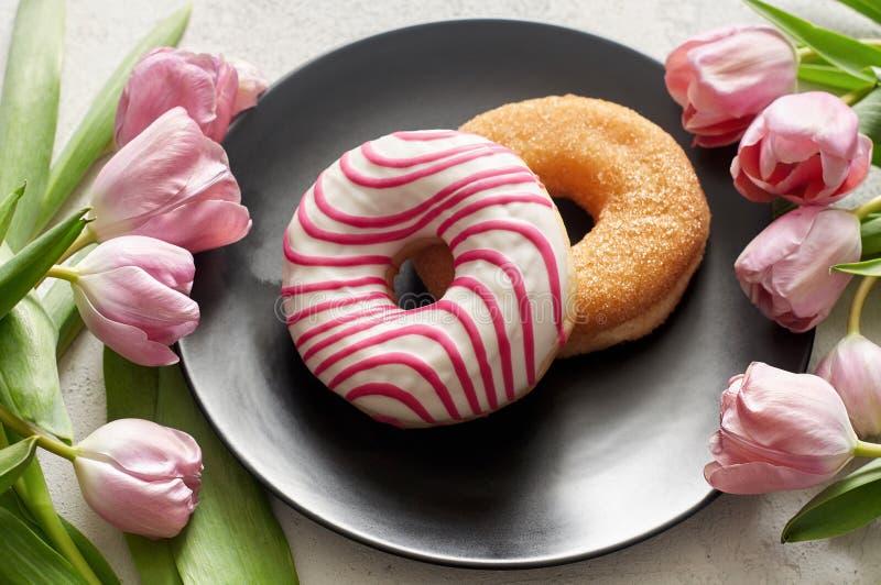 糖和给镶边上釉的油炸圈饼与郁金香在黑色的盘子 库存照片