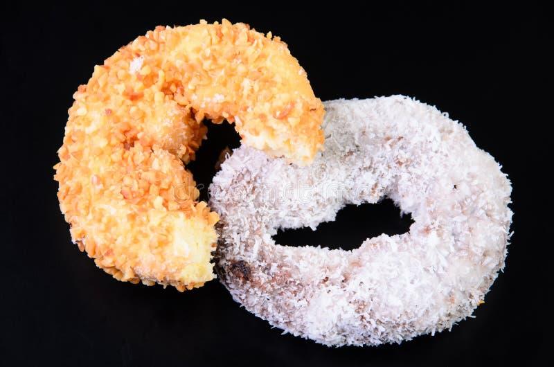 糖在黑背景的圆环多福饼 库存图片