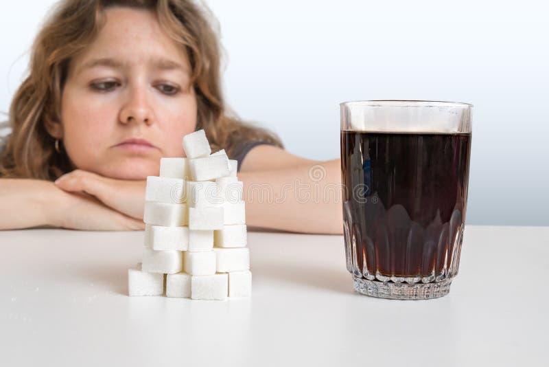 糖尿病妇女在与可乐糖饮料和堆的玻璃看  概念吃不健康 库存照片