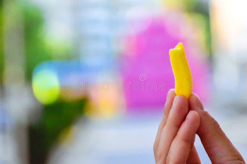 糖果咬住在手中,有五颜六色的背景 库存图片