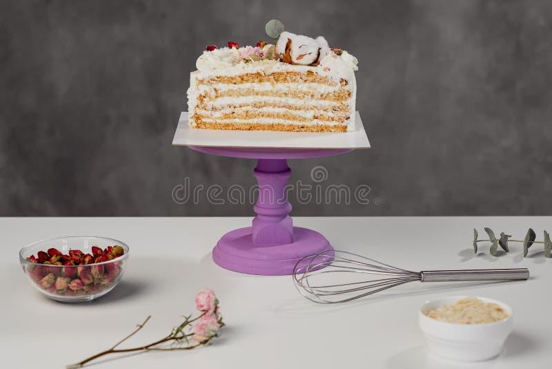 糖果商的桌 被切开的白色吹蛋糕和酥皮点心工具 库存图片