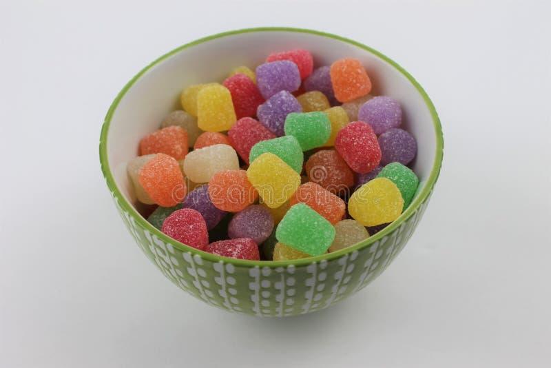 糖果在一个装饰绿色和白色玻璃碗的胶下落在被隔绝的白色背景 图库摄影
