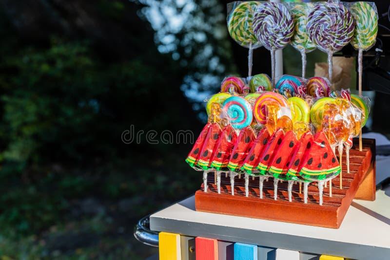 糖果店和五颜六色的candys 糖果,棒棒糖,在strret商店的糖果 复制空间 不健康的食物 .30-06步枪螺栓和范围特写镜头在camo背景 免版税库存照片