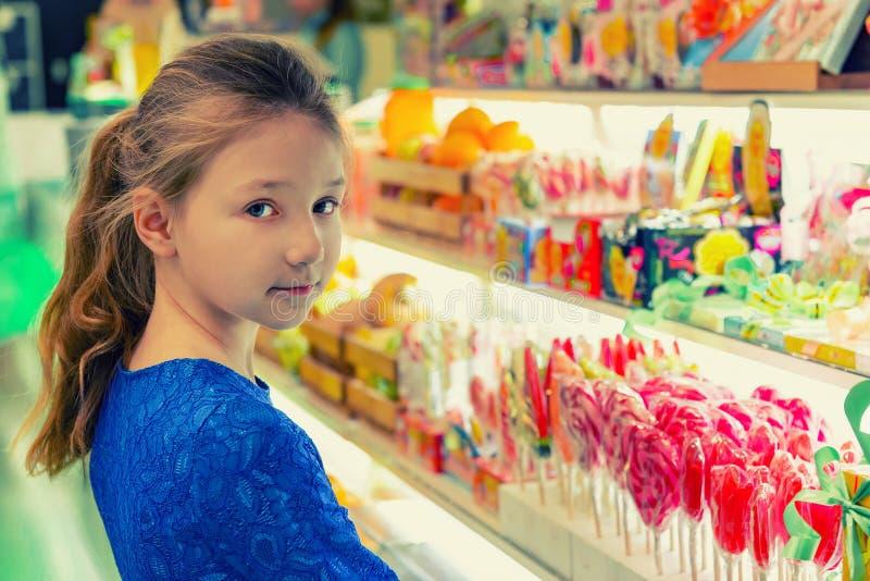 糖果店的一个女孩选择多彩多姿的糖果和棒棒糖 库存图片