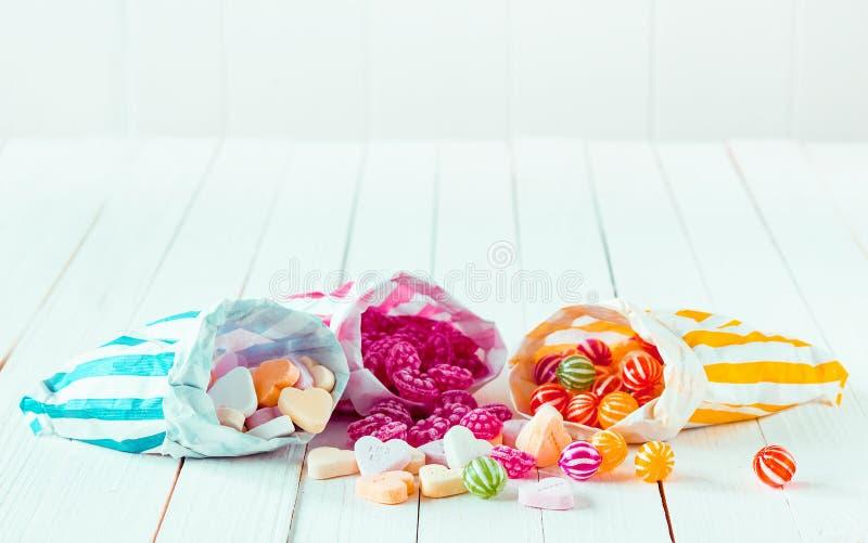 糖果的分类在三个袋子的在桌 免版税图库摄影