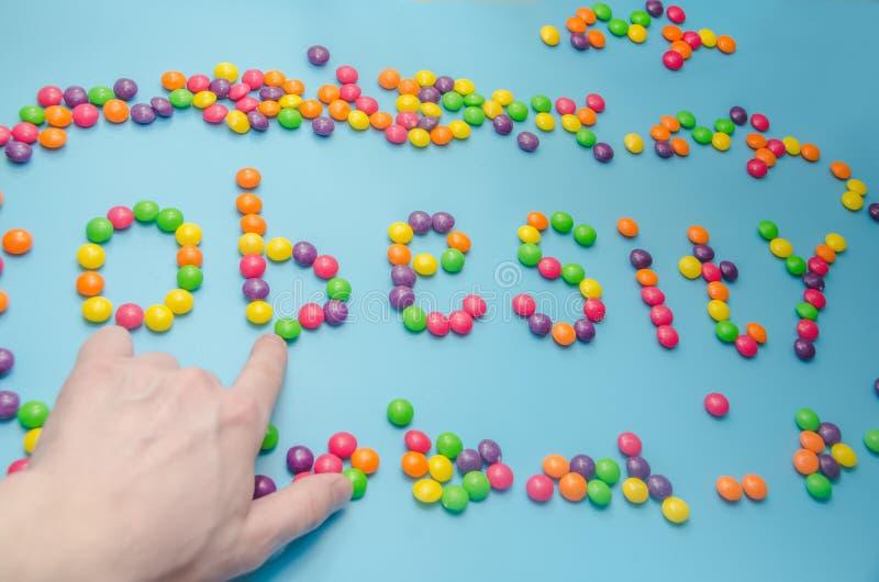 糖果,焦糖糖特写镜头涂上了肥胖病,在蓝色backgrou 免版税图库摄影