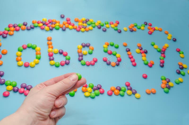 糖果,焦糖糖特写镜头涂上了肥胖病,在蓝色backgrou 免版税库存照片
