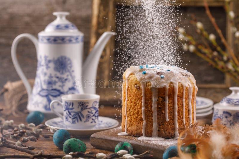 糖粉末倾吐在复活节蛋糕上 静物画作为对复活节的一张明信片 在一个土气样式的复活节装饰与vinta 免版税图库摄影