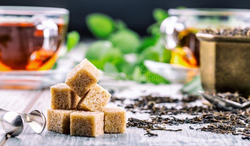 糖 蔗糖 蔗糖立方体堆积紧密宏观射击 在一个玻璃杯子的茶,薄荷叶,干茶,被切的石灰,藤茎褐色 库存图片