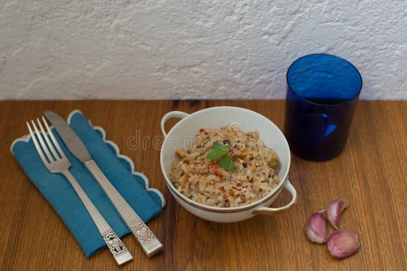 糙米意大利煨饭在白色和金子颜色的中国瓷盘服务与银色利器蓝色亚麻布餐巾蓝色玻璃 免版税库存图片