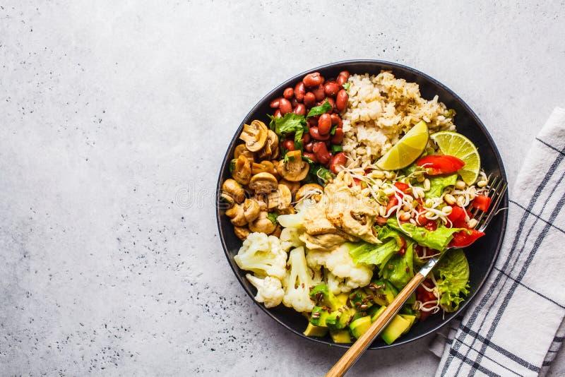 素食午餐 糙米用蘑菇、豆、沙拉和hummus在黑色的盘子,干净的eatind 图库摄影