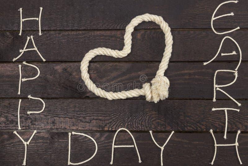 系住在爱心脏形状与文本的:愉快的世界地球日 库存图片
