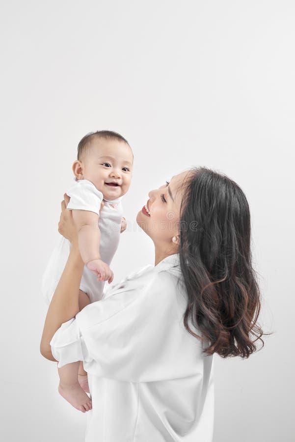 系列愉快爱 拥抱笑的婴孩的年轻微笑的母亲 免版税库存图片
