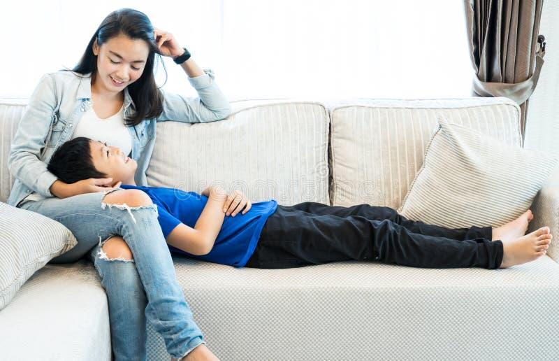 系列愉快的时间 放松在客厅的母亲和儿子 免版税库存照片
