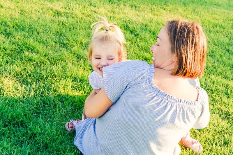 系列愉快的本质 妈妈和小孩放松小的女儿,拥抱,笑和获得在绿草草甸的乐趣在平衡su 免版税图库摄影