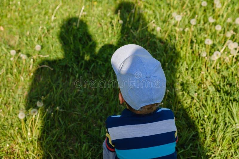 系列的概念 父母、父母的阴影保护孩子免受烧焦的太阳 图库摄影