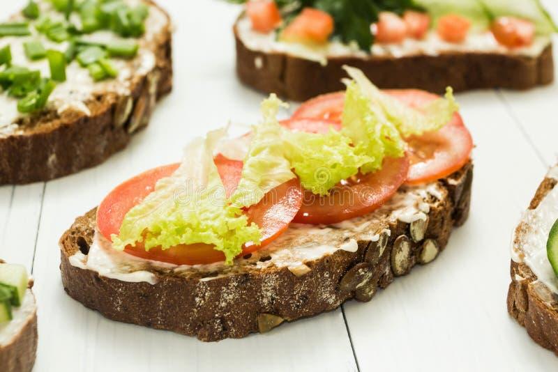 素食三明治的分类与菜和乳酪的在一张白色桌上 库存图片