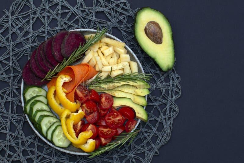 素食主义者、菩萨戒毒所碗食谱用鲕梨,红萝卜、黄瓜、甜菜、黄色胡椒、蕃茄和白萝卜 顶视图,平的拷贝空间 库存照片