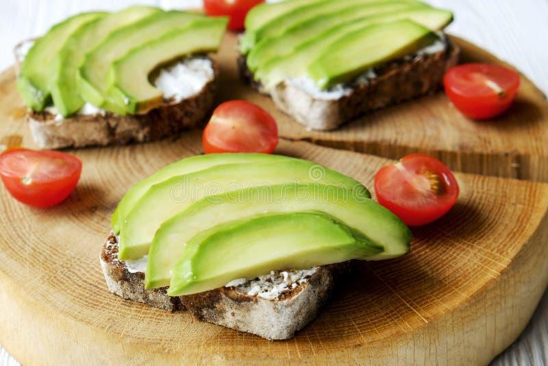 素食主义者三明治,黑麦面包多士,鲕梨,西红柿,在厚实的破裂的木切片,白色的vegenaise eggless蛋黄酱调味汁求爱 免版税图库摄影