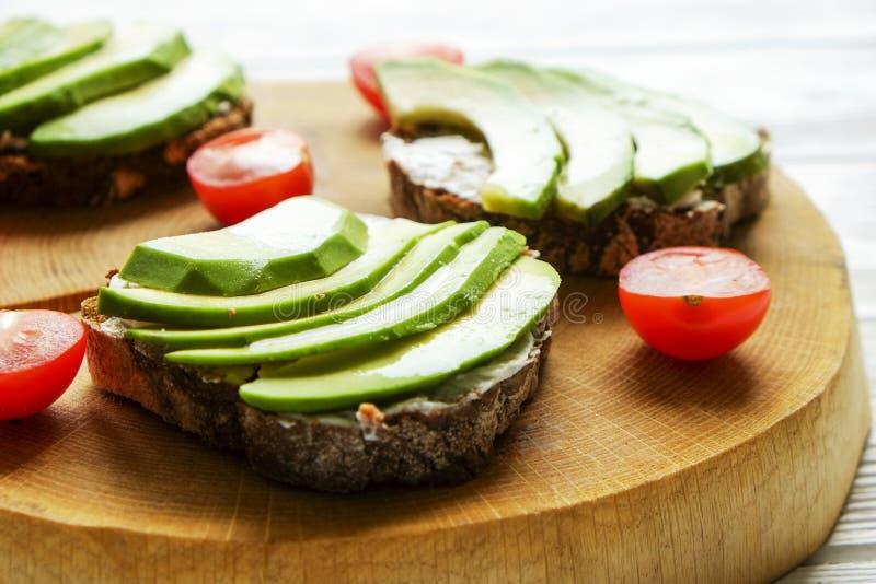素食主义者三明治,黑麦面包多士,鲕梨,西红柿,在厚实的破裂的木切片,白色的vegenaise eggless蛋黄酱调味汁求爱 图库摄影