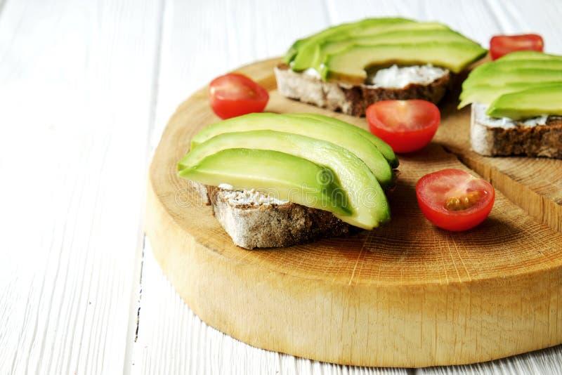 素食主义者三明治,黑麦面包多士,鲕梨,西红柿,在厚实的破裂的木切片,白色的vegenaise eggless蛋黄酱调味汁求爱 库存照片