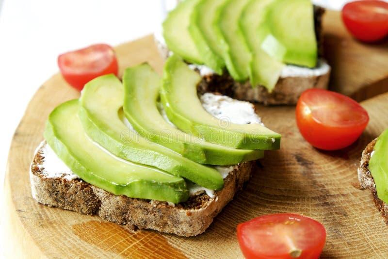 素食主义者三明治,黑麦面包多士,鲕梨,西红柿,在厚实的破裂的木切片,白色的vegenaise eggless蛋黄酱调味汁求爱 库存图片