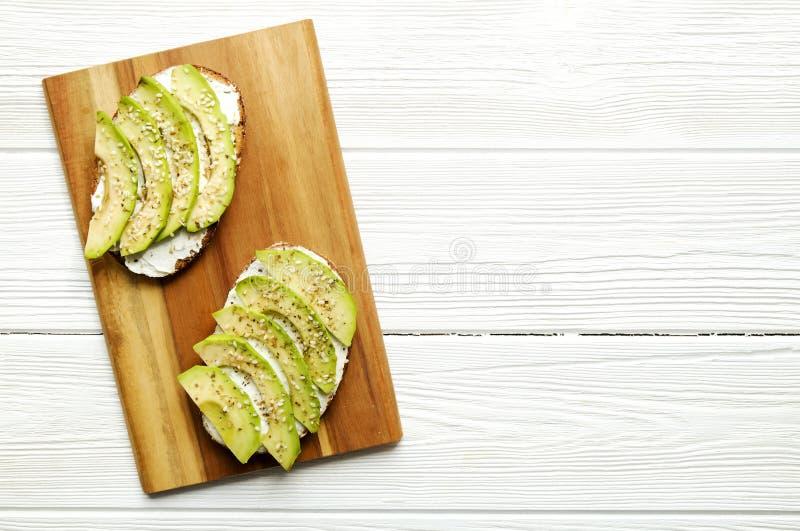 素食主义者三明治,黑麦面包多士,鲕梨, vegenaise eggless蛋黄酱调味汁,晒干的芝麻籽,白色木纹理桌 Ve 库存照片