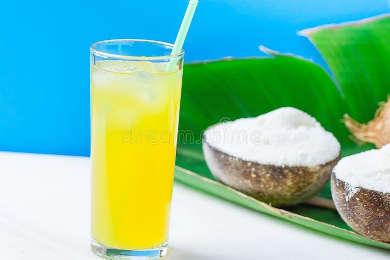 素食主义者在碗的椰子饯奶油在大绿色棕榈叶玻璃用在白色大理石表蓝色背景的热带水果汁 库存图片