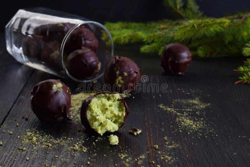 素食主义者在黑暗的木背景的鲕梨块菌 与椰子和茶matcha的未加工的能量叮咬 自创巧克力糖 健康 库存图片