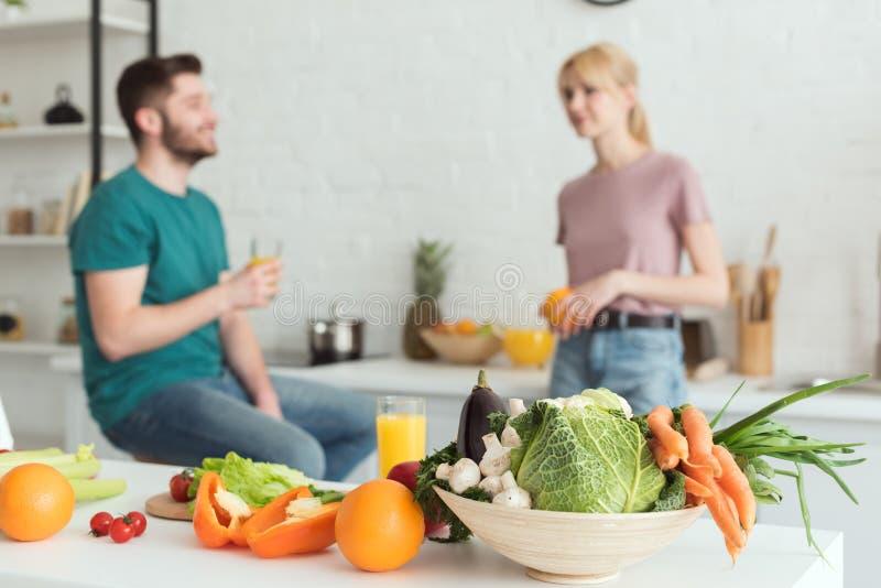 素食主义者夫妇谈话在厨房里用水果和蔬菜 免版税图库摄影