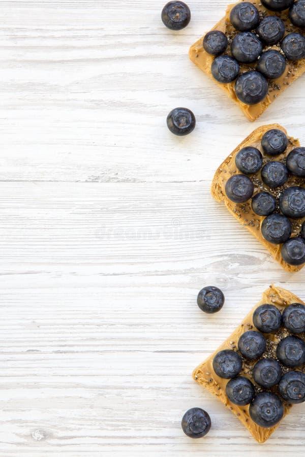 素食主义者敬酒用花生酱、蓝莓和chia种子在一张白色木桌,顶视图上 吃健康 平的位置,从abov 库存图片