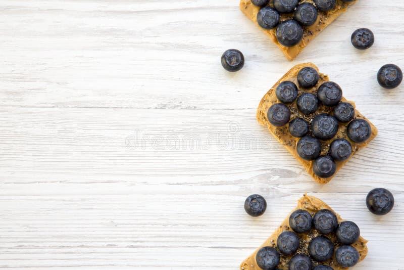素食主义者敬酒用花生酱、蓝莓和chia种子在白色木背景,顶视图 吃健康 平的位置,从 免版税库存照片