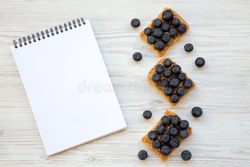 素食主义者敬酒用花生酱、蓝莓和chia种子在白色木背景,顶视图 吃健康 平的位置,从 库存照片