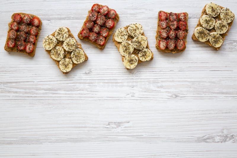 素食主义者敬酒用花生酱、香蕉、草莓和chia种子白色木表面上,从上面 健康的早餐 免版税库存照片