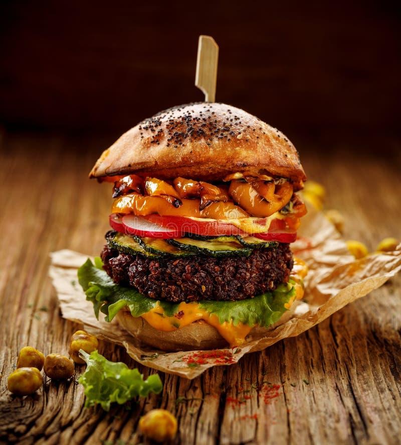 素食主义者汉堡、甜菜根汉堡、自创汉堡用甜菜根炸肉排,烤胡椒、夏南瓜、萝卜、莴苣和咖喱汁  免版税库存图片