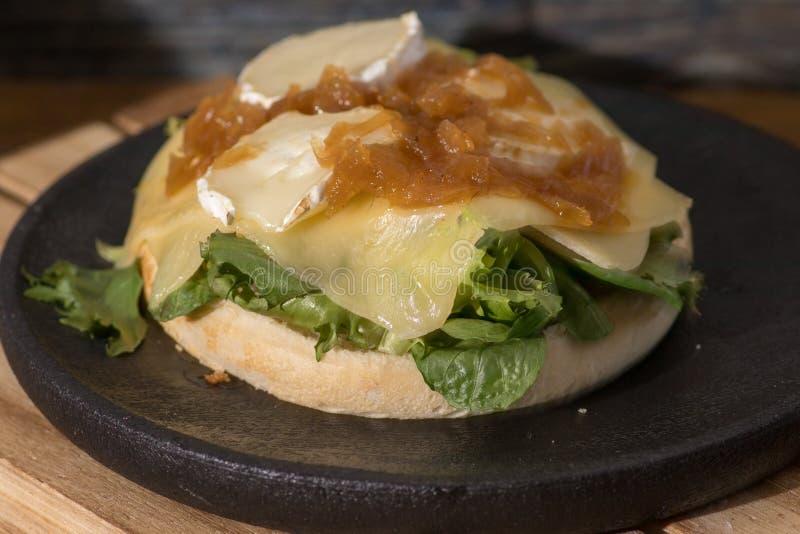 素食主义者汉堡包用乳酪和番茄酱在黑木板材 免版税库存图片