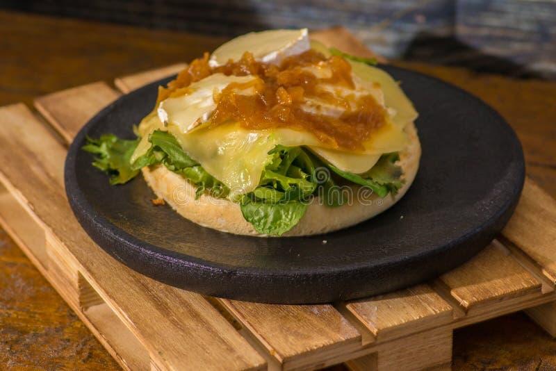 素食主义者汉堡包用乳酪和番茄酱在黑木板材 库存图片
