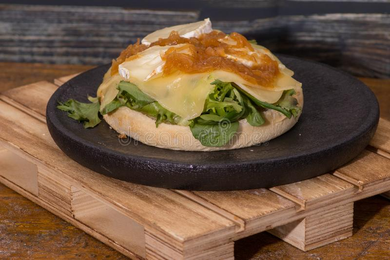素食主义者汉堡包用乳酪和番茄酱在黑木板材 库存照片