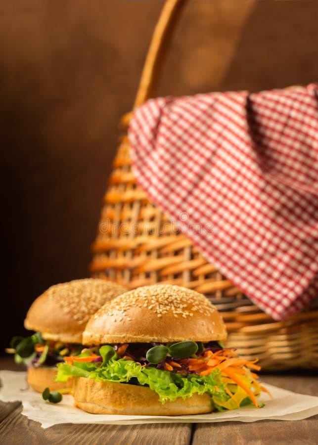 素食主义者汉堡新鲜蔬菜:红萝卜,莴苣年轻新芽绿色黑暗的木土气背景 垂直的框架 库存照片
