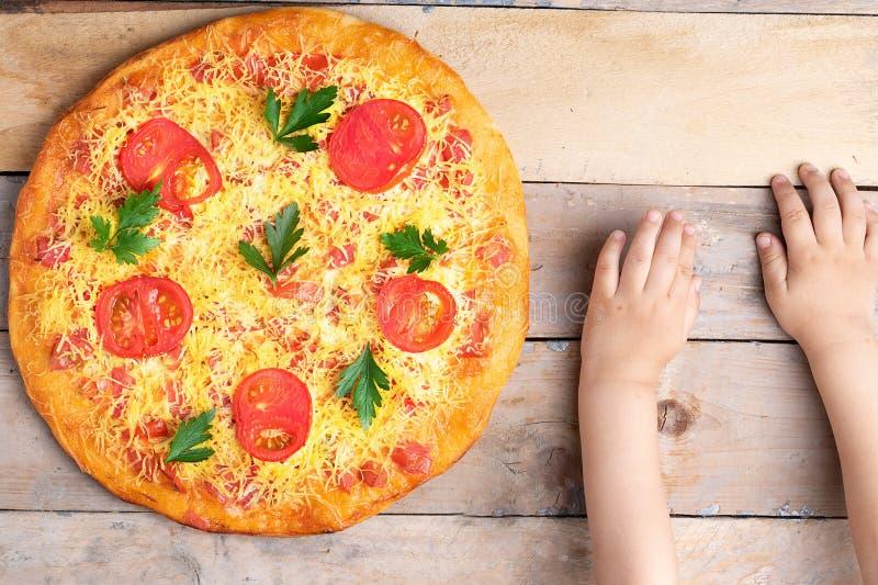素食主义者玛格丽塔酒比萨用在木桌上的孩子手,顶视图 图库摄影