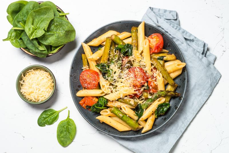 素食主义者面团penne用菠菜、芦笋和蕃茄 免版税库存图片