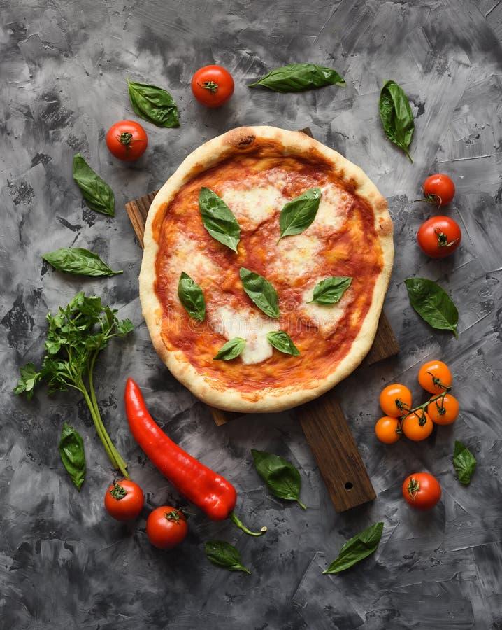 素食土气比萨马尔盖里塔Flatlay与未加工的成份的在黑暗的背景 免版税库存照片