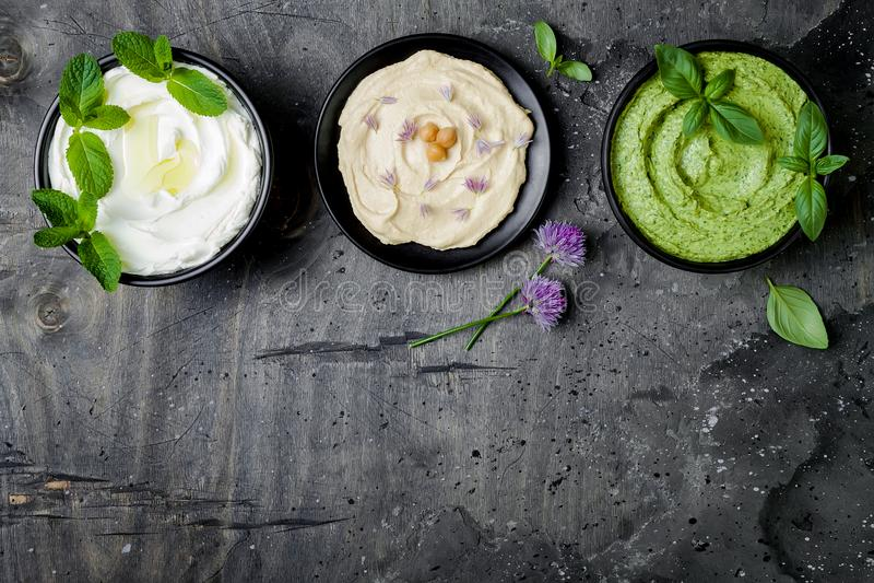 素食垂度桌 酸奶调味汁或labneh、hummus、草本hummus或者pesto 被设置的中东meze快餐 免版税库存照片
