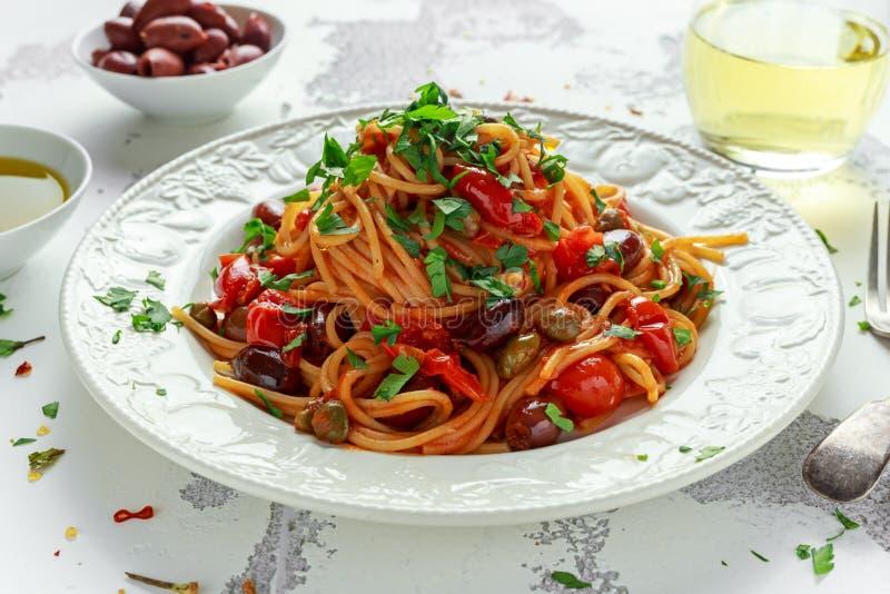 素食意大利面团Alla Puttanesca用大蒜,橄榄,与在白色板材的雀跃 库存照片