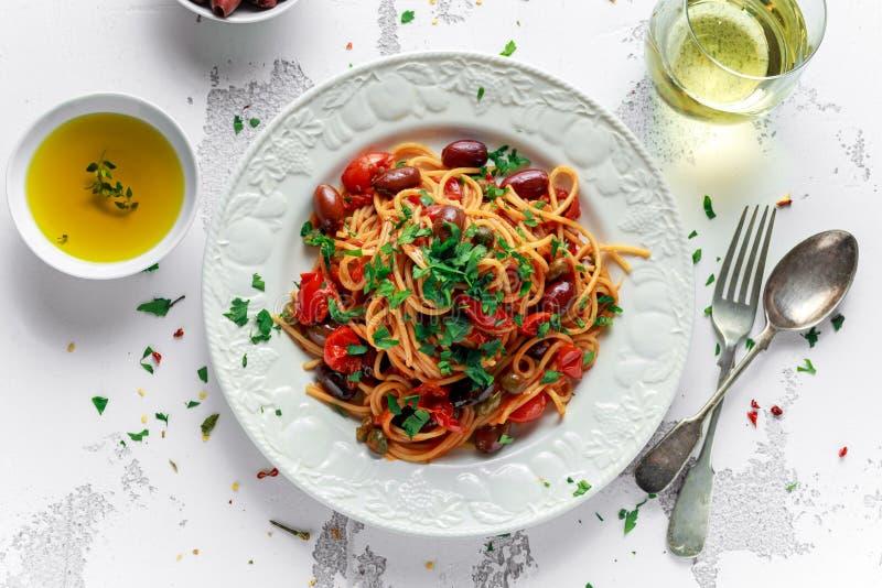 素食意大利面团Alla Puttanesca用大蒜,橄榄,与在白色板材的雀跃 库存图片
