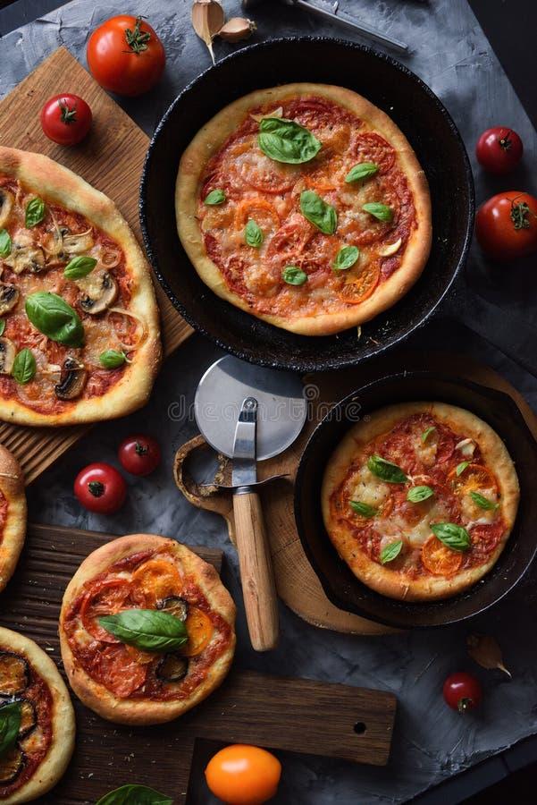 素食比萨党Flatlay  自创土气比萨用蕃茄、蘑菇、甜椒、茄子和蓬蒿在生铁 图库摄影