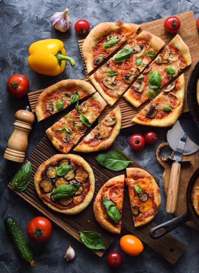 素食比萨党Flatlay  自创土气比萨用蕃茄、蘑菇、甜椒、茄子和蓬蒿在黑暗 库存照片